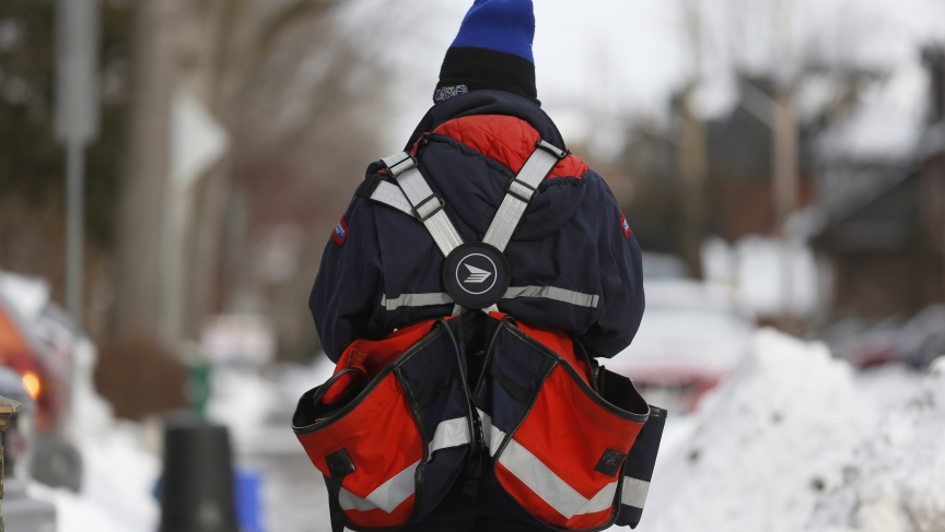 A Canada Post employee delivers mail in Ottawa December 11, 2013.